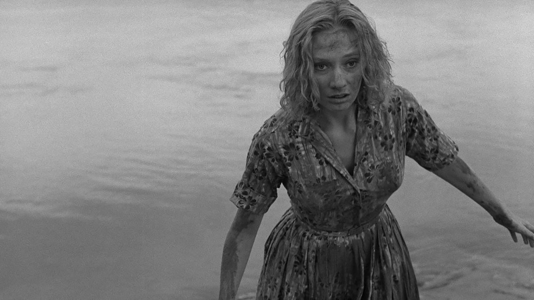 Medium close shot of a young, blond white woman in a damp, muddy midcentury-style dress stagger out of a lake