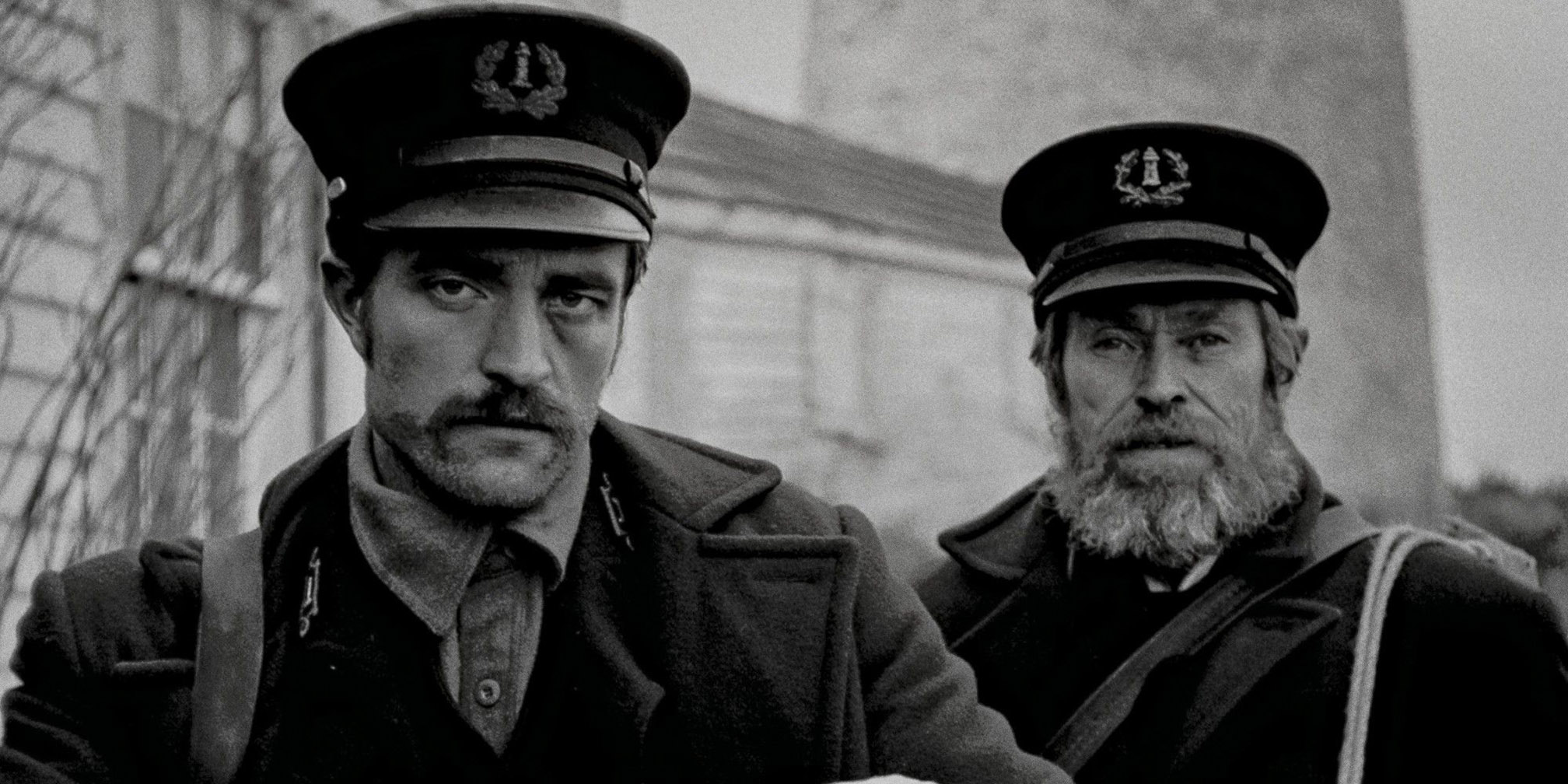 Two white men, one young with a mustache and one old with a beard, wear dark uniforms and stare straight ahead