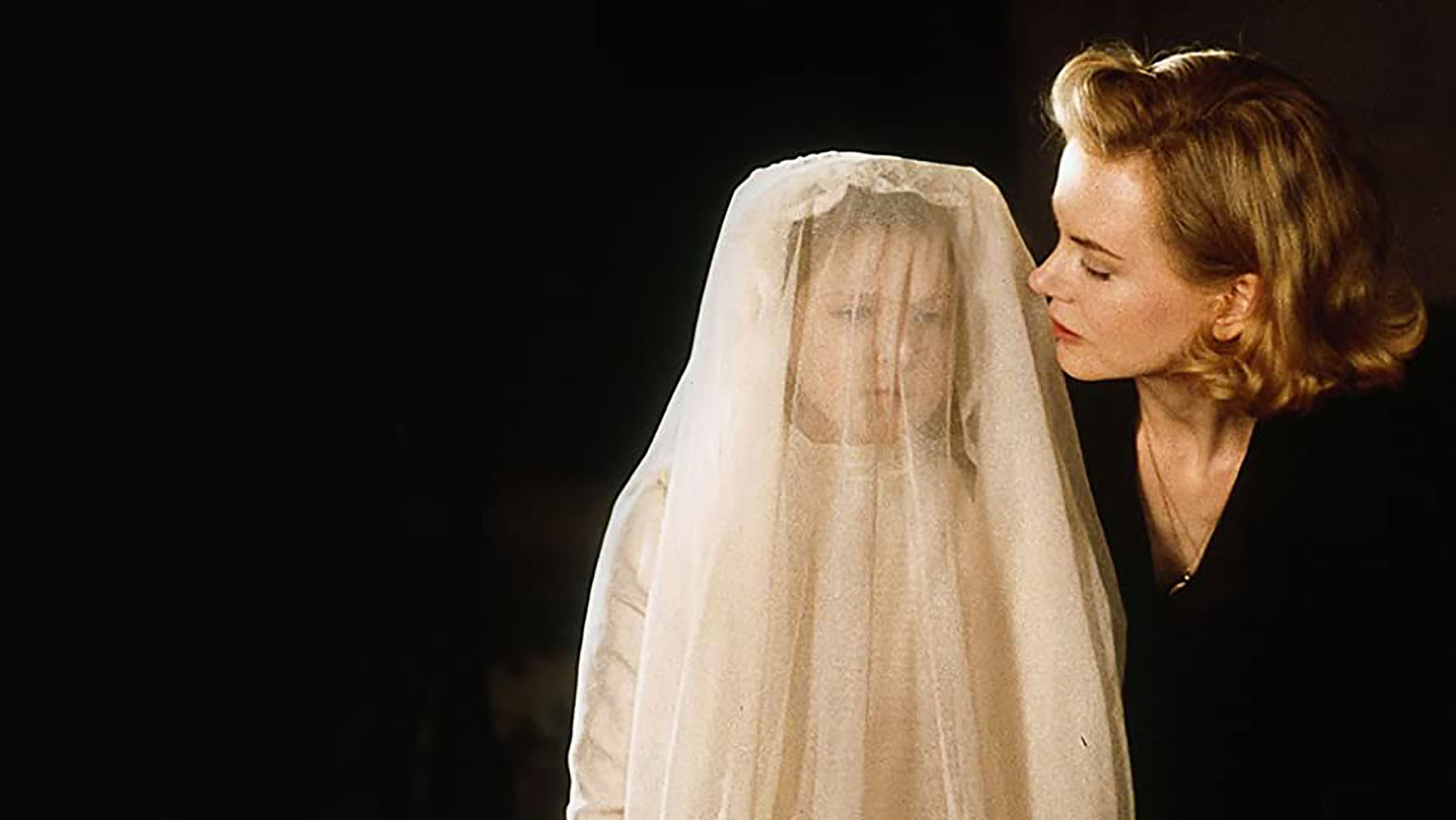 A little white girl in a white veil looking concerned next to her mother, a young white woman with a sleek 1940s blond hairstyle