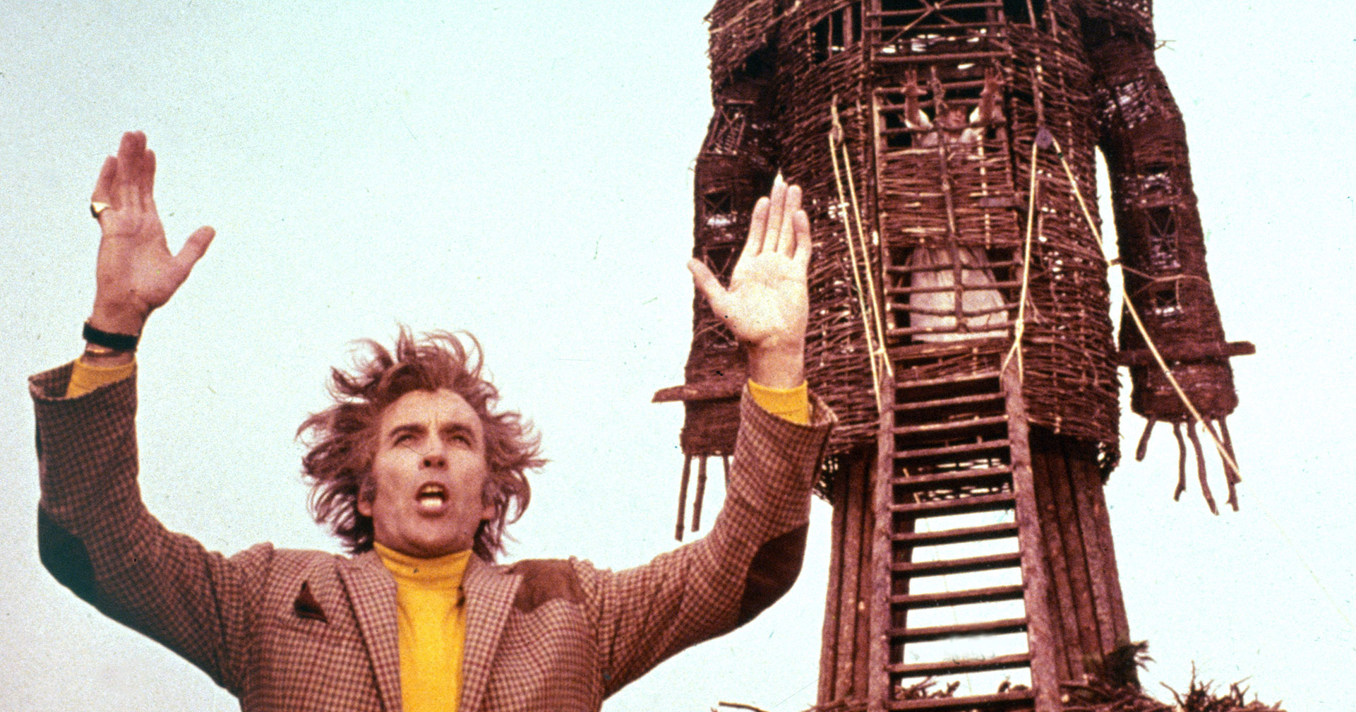 A middle-aged white man in a tweed jacket and yellow turtleneck, his hair blowing wildly in the wind, raise his arms in front of a large man made of wood