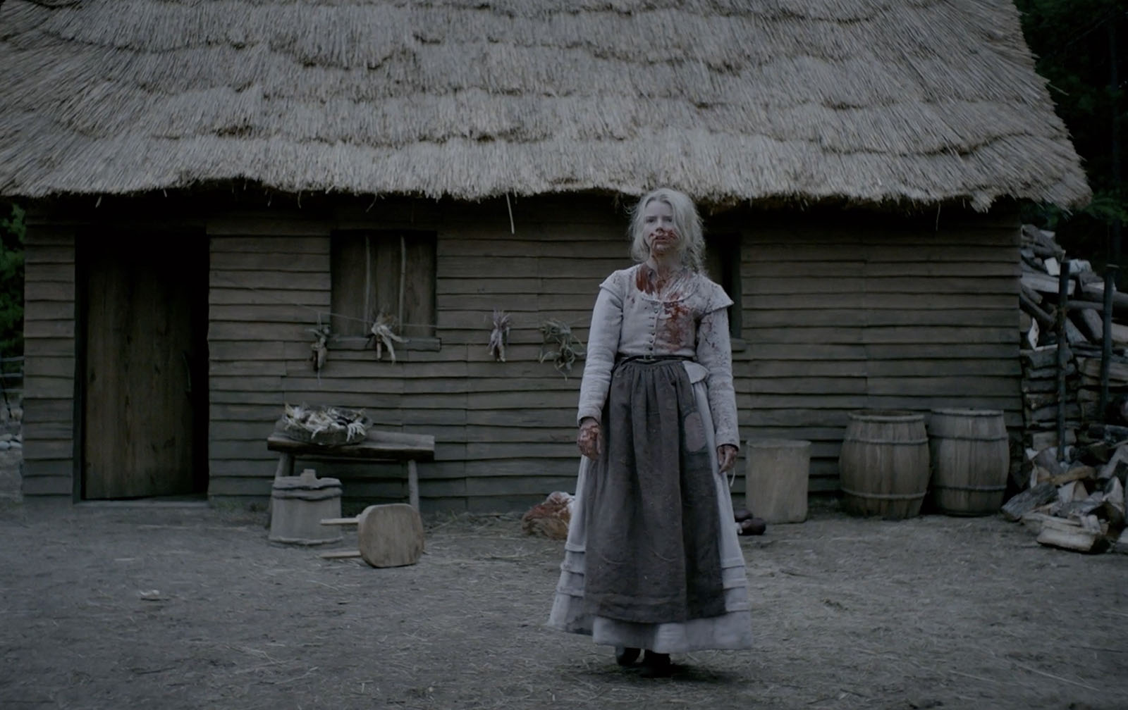 Screenshot from THE WITCH of a white young girl in 1600s clothes standing dazed and bloodied outside of a rustic house
